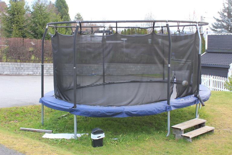 zahradní trampolína střední velikosti s modrým ochranným krytem
